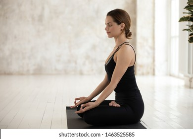 Side view serene young pretty woman wear black sportswear sitting in lotus position closed eyes meditating indoors, do Siddhasana asana accomplished pose, concept of yogic practices, healthy lifestyle