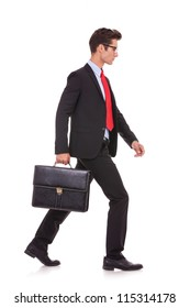 side view of a serious business man holding a briefcase and walking forward on white background