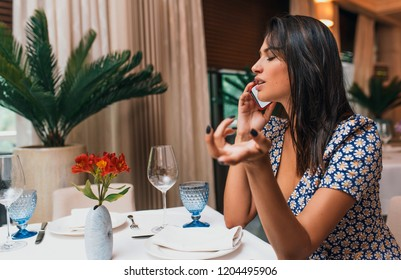 Side view of serious business woman talking on smart phone with clients indoor in a restaurant. Image of smart young female have a call on her mobile phone in a cafeteria.