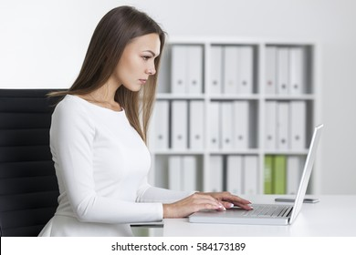 Side view of a serious businesswoman wearing white clothes and typing at her laptop keyboard in an office with white and green binders.