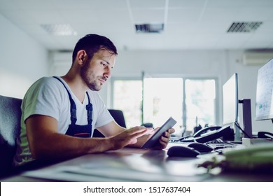 Side view of serious caucasian plant worker using tablet while sitting in control room.