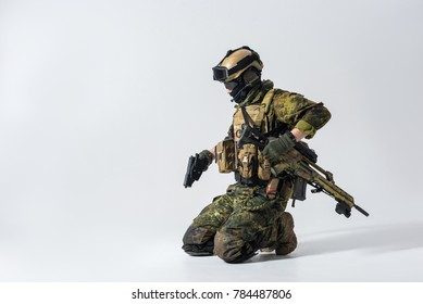 Side view serious defender holding pistol in arms while locating on knee. Protection concept. Copy space