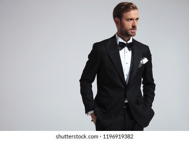 side view of a serious elegant man wearing tuxedo and standing with hands in pockets on grey background