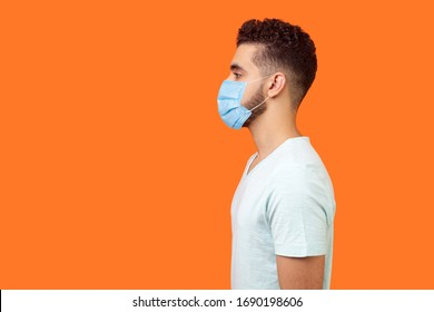 Side view of serious handsome brunette man with surgical medical mask standing with hands down and looking left, empty copy space for text. indoor studio shot isolated on orange background