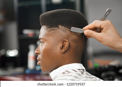Side view of serious man with stylish modern haircut looking forward in barber shop. Hand of barber keeping straight razor and cutting trendy stripes on head of client. Concept of shaving.