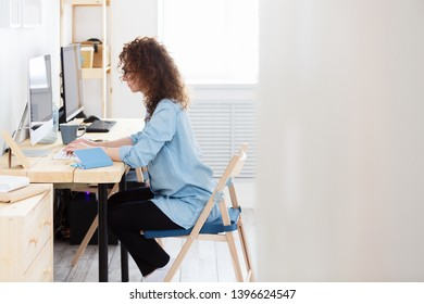 Side view serious redhead woman accountant analyzes information from web page,checks accounting documentation in online database