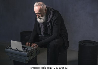 Side view serious unshaven old author typing in printing machine while sitting on black barrel. Inspiration concept. Copy space
