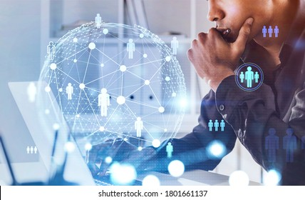 Side view of serious young African American businessman using laptop in blurry office with double exposure of social network interface. Concept of HR. Toned image
