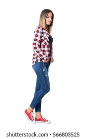 Side view of serious young beautiful girl with hands in pockets walking and looking down. Full body length portrait isolated over white studio background.