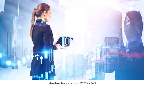 Side view of serious young businesswoman using laptop in abstract city with double exposure of blurry financial graph. Stock market concept. Toned image