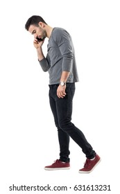 Side view of serious young casual man walking and talking on the phone looking down. Full body length portrait isolated over white studio background.