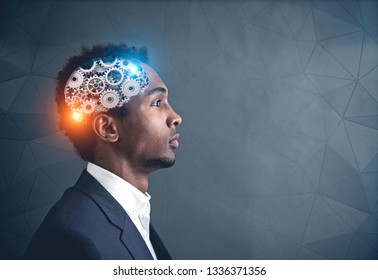 Side view of serous young African American businessman in suit with gear brain inside his head. Geometric pattern wall background. Mock up