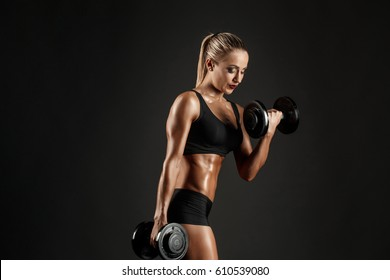 Side view of sexual blonde with ponytail in bikini posing with dumbbells on black background.