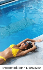 Side view of sexy tanned woman in yellow bikini and sunglasses lying down summer day near poolside. Sensual young female model sunbathing at swimming pool, smiling enjoying summertime resort.