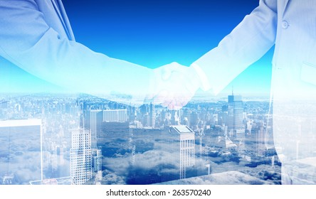 Side view of shaking hands against high angle view of city skyline