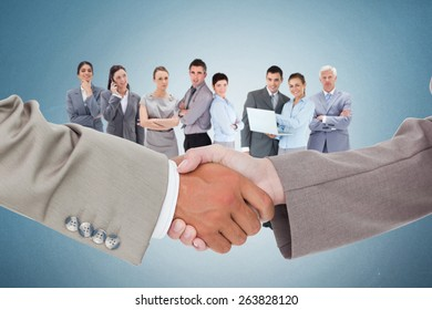 Side view of shaking hands against blue