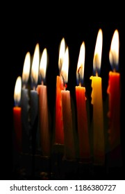 Side view with shallow depth of field of a fully lit menorah on a black background. The candles are a various colors and are glowing from the candle flame. Nice Hannukah image.