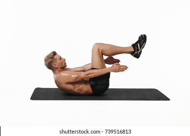 Side view of shirtless sportsman doing knee crunches while lying on mat on white background.