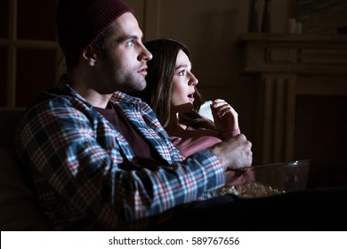 side view of shocked couple watching movie together at home