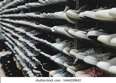 Side view of shoe store shelves with of lots of sneakers on sale. Low-budget comfortable footwear shopping. Unisex stylish teenager shoes. Rows of new runners in shoe shop. Stands of cheap trainers.