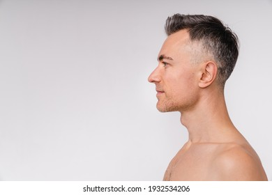 Side view shot of an attractive mature naked man isolated over white background