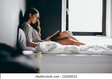 Side view shot of an attractive young woman sitting on her bed reading an interesting novel. Caucasian female model in bedroom reading a book.