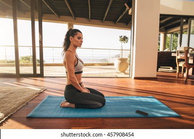 Side view shot of beautiful young woman sitting in yoga pose at home. Fitness female doing meditation on exercise mat in living room of her apartment.