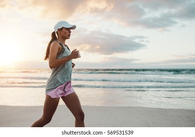 Side view shot of beautiful young woman in sportswear jogging on beach. Female runner jogging on outdoors on beach.