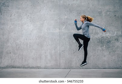 Side view shot of fit young woman doing cardio interval training against grey background. Fitness female exercising outdoors in morning.