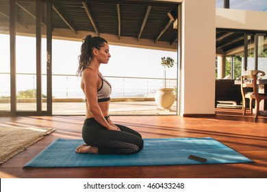 Side view shot of fitness woman sitting in yoga pose at home. Female in sportswear doing meditation on exercise mat in living room of her apartment.