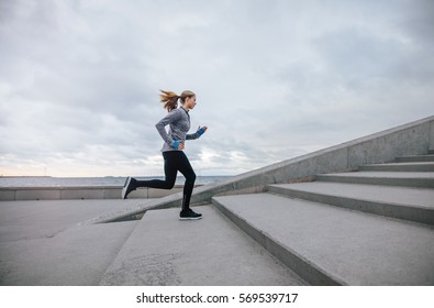 Side view shot of fitness woman running up on steps. Female runner athlete going up stairs.