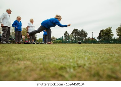 A side view shot of a group of senior friends lawn bowling on grass, with one woman who has taken her shot.