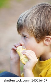 Side view shot of little boy eating corn on the cob