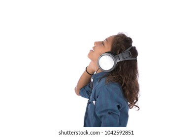 A side view shot of a little kid wearing a headphone feeling amused while listening to music, isolated on a white background.