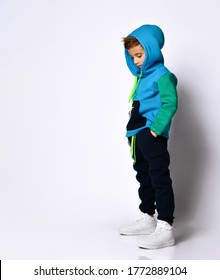Side view shot of little schoolboy in bright cotton tracksuit standing with hands in pockets looking down. Children fashion, young athletes, being stylish. Full length portrait isolated on light grey