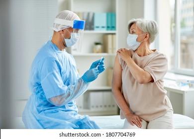 Aufnahme der männlichen Krankenschwester mit Schutzmaske und Handschuhen, die eine medizinische Spritze zur Injektion an ältere Patienten vorbereiten
