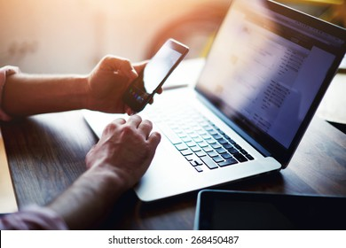 Side view shot of a man's hands using smart phone in interior, rear view of business man hands busy using cell phone at office desk, young male student typing on phone sitting at wooden table, flare - Shutterstock ID 268450487