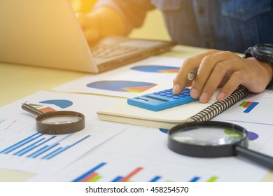 Side view shot of a man's hands using laptop in interior, rear view of business man hands busy using calculator at office desk