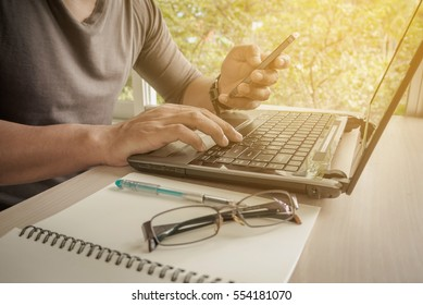 Side view shot of a man's hands using smart phone, rear view of business man hands busy using cell phone, young male student typing on phone sitting at wooden table.