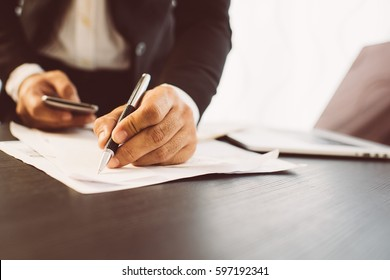 Side view shot of a man's hands using smart phone in interior, rear view of business man hands busy using cell phone at office desk