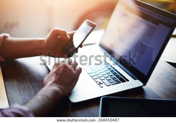 Side view shot of a man's hands using smart phone in interior, rear view of business man hands busy using cell phone at office desk, young male student typing on phone sitting at wooden table, flare