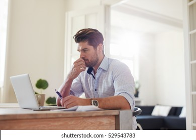 Side view shot of pensive young man sitting at home and working on laptop. Caucasian male working from home office.