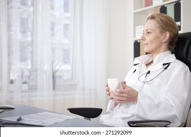 Side View Shot of a Thoughtful Medical Doctor Holding a Cup of Drink While Sitting on a Chair at her Office and Looking Afar.