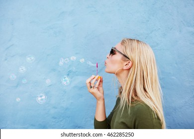 Side view shot of young beautiful female blowing soap bubbles against blue background. Young blond woman having fun.