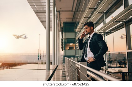 Side view shot of young businessman standing on airport lounge balcony and talking on mobile phone. Handsome caucasian male waiting for his flight.