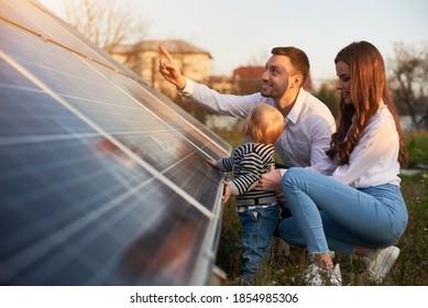 Seitenansicht einer jungen modernen Familie mit einem kleinen kleinen Jungen, der an einem sonnigen Tag mit Sonnenkollektoren vertraut wird, grünes Alternativenergiekonzept