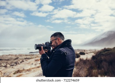 Side view shot of young photographer photographing outdoors. Man taking a photos with dslr camera outdoors. Photographer taking travel nature photography.