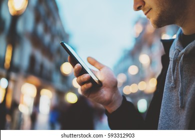 Side view shot of young smiling man using smartphone at night city street, bokeh lights, hipster guy chatting with friends at social networks via cellphone outdoor, visual effects