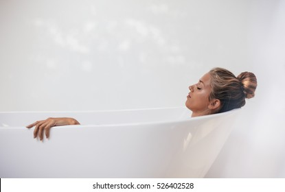 Side view shot of young woman lying in bathtub with her eyes closed. Female relaxing in bathtub.