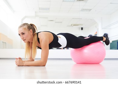 Side view shot of young woman in white and black sports wear doing plank exercise on fitball